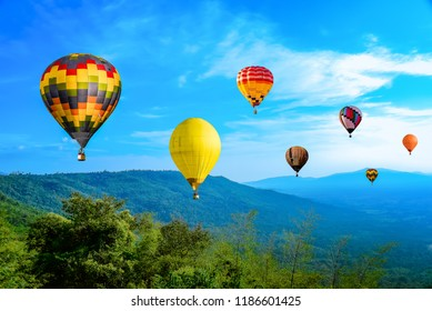 Colorful hot air Balloons  flying above green mountain with  beautiful blue cloudy sky background