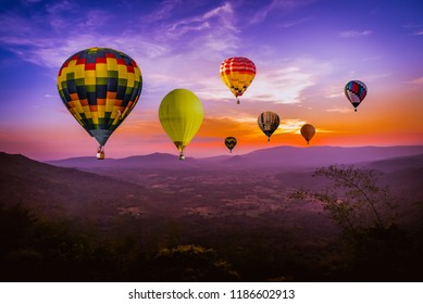 Colorful hot air Balloons  flying above green mountain at sunset time with  beautiful twilight sky background