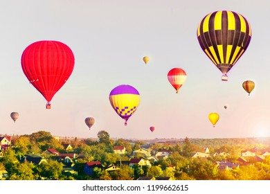 Colorful hot air balloons flying over city