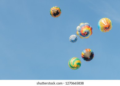Colorful hot air balloons flying over blue sky