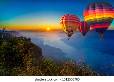 Colorful hot air balloons flying in sunrise over mountain and Ping River at Pha Daeng Luang, Mae Ping National Park, Lamphun in Thailand