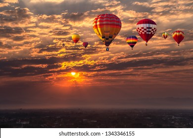 Colorful hot air balloons flying above sunset over buildings in Chiang Mai, Thailand.