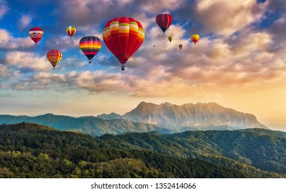 Colorful hot air balloons flying above high mountain at sunrise with beautiful sky background