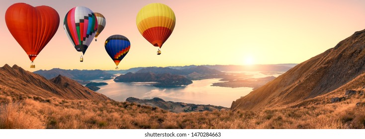 Colorful hot air balloons flying above high mountain at sunrise with beautiful sky background in roys peak track, New Zealand. Panorama of mountain with hot air balloons on morning
