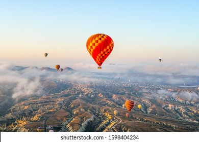 Colorful hot air balloons flying over  stunning nature landscape of Cappadocia, Turkey with morning sky and white mist