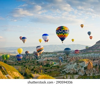 Colorful hot air balloons flying over Red valley at Cappadocia, Anatolia, Turkey. Volcanic mountains in Goreme national park.