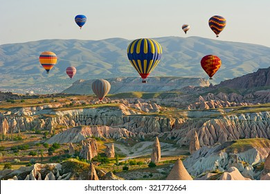 Colorful hot air balloons flying over the valley at Cappadocia, Anatolia, Turkey. Volcanic mountains in Goreme national park.