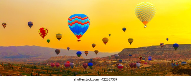Colorful Hot Air balloons flying over Mountains landscape silhouette with sunrise Cappadocia, Turkey
