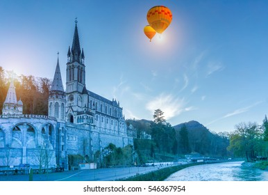 Colorful hot air balloons flying over Rosary Basilica in the evening, Lourdes, Hautes-Pyrenees, France