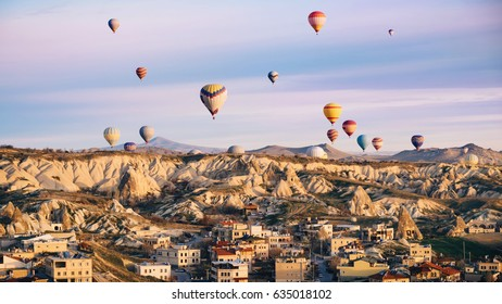 Colorful hot air balloons flying over the city at Cappadocia, Turkey. Volcanic mountains in Goreme national park in the morning.