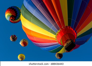 Colorful hot air balloons flying in the sky with the blue sky in the background.