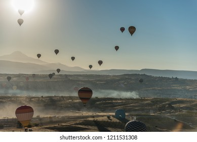 Colorful hot air balloons landing on the ground in Cappadocia, Turkey