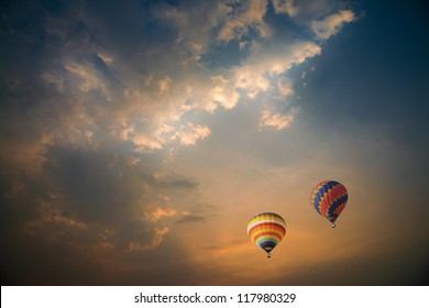 Colorful hot air balloons over the dramatic sky during sunset