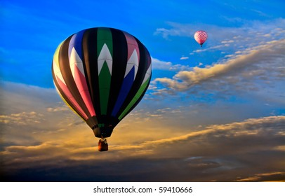 Colorful hot air balloons at sunset. Deep blue and gold sky and clouds. View from air as balloons float in the air current.