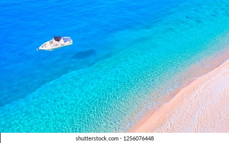 Colorful Hot Summer Landscape of Kaputas Beach - Motorboat on the crystal clear sea with boat's shadow - Antalya Turkey