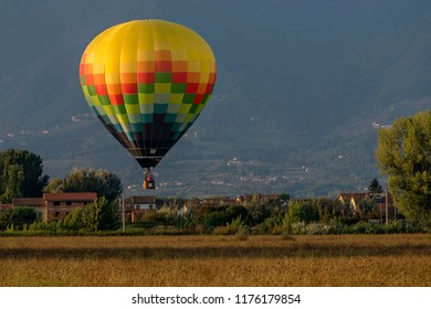 Colorful hot-air balloon flies over typical village in the Tuscan countryside in the light of the sunset