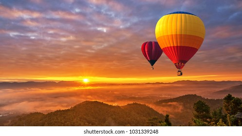 Colorful hot-air balloons flying over misty morning sunrise at Chiang Mai, Thailand.