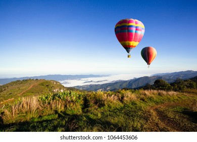 Colorful hot-air balloons flying over the mountain with sunrise and morning Thailand.