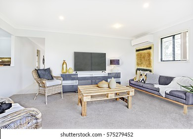 Colorful house with facilities and designs, comfortable furniture with designs, walls are white color, pillows on chairs, inside room of a apartment.