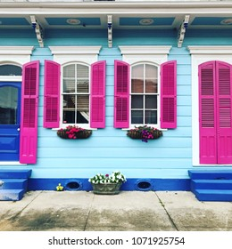 Colorful house in New Orleans, Louisiana. Facade of house has fuchsia window shutters, cobalt blue steps and light blue wood paneling.