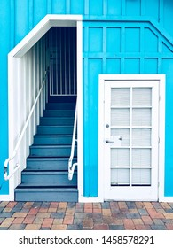Colorful house wall with white door and a stairway