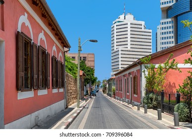 Colorful houses along narrow street as modern buildings on background under blue sky in Neve Tzedek neighborhood in Tel Aviv, Israel.