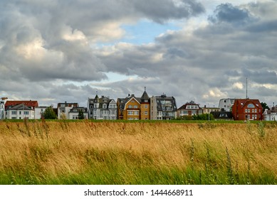 colorful houses behind the dike and a meadow with long yellow grass in Cuxhaven (Germany) under a vivid cloudy sky