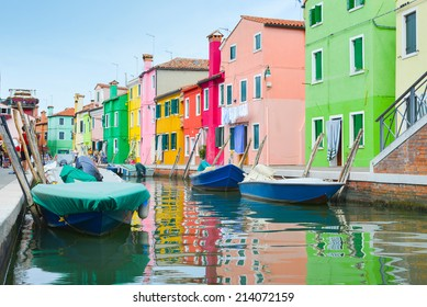 Colorful houses and boats in Burano village on sunset near Venice, Italy