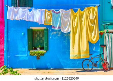 Colorful houses in Burano and airing linen in the street, Venice, Italy