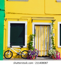 Colorful houses in Burano with a bike standing next to a flower decorated door