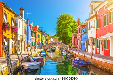 Colorful houses of Burano island. Multicolored buildings on fondamenta embankment of narrow water canal with fishing boats and stone bridge, Venice Province, Veneto Region, Italy. Burano postcard - Shutterstock ID 1807343104