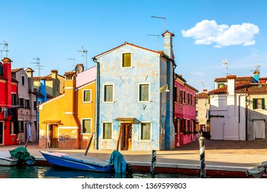 Colorful houses in Burano near Venice, Italy with boats and beautiful blue sky in summer. Famous tourist attraction in Venice.