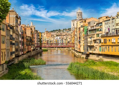 Colorful houses, Eiffel bridge and Saint Mary Cathedral at background in Girona, in a beautiful summer day, Catalonia, Spain