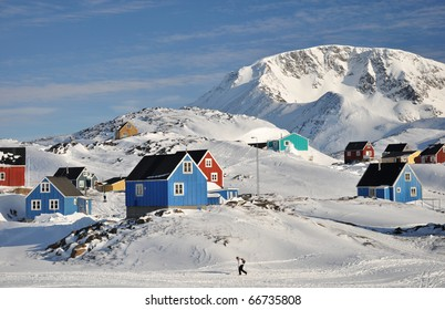 Colorful houses in the Kulusuk village and walking person, Greenland