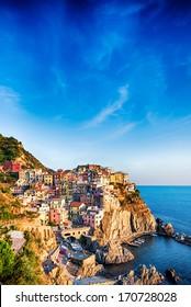 Colorful houses of Manarola Cinque Terre under a blue sky, Liguria, Italy