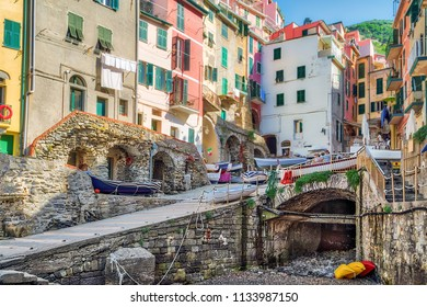 colorful houses overlooking rocks of the marina of Riomaggiore, sea village of Cinque Terre in Italy