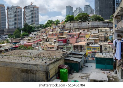 Colorful houses of the poor inhabitants of Luanda, Angola. These ghettos resemble Brazilian favelas. In the background the high rise buildings of the rich build a stark contrast.