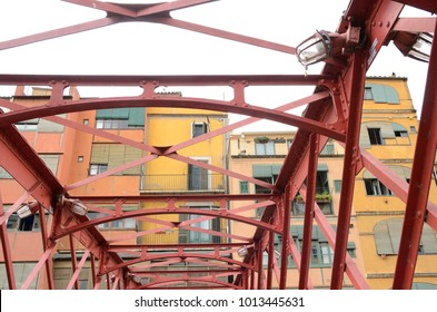 Colorful houses and red iron bridge in Girona, Catalonia, Spain.
