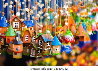 Colorful house-shaped ceramic hanging bells in the handicraft mart of Kaziukas, Vilnius, Lithuania. Beautiful funny symbol of home, clay, houses, colors and real estate.