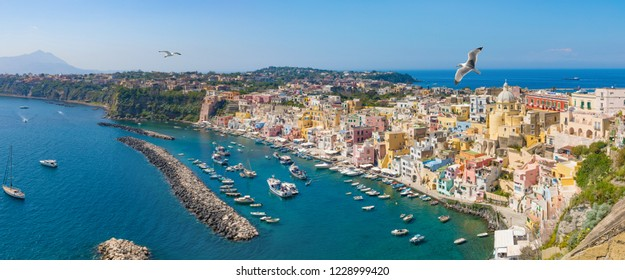 Colorful housing, fishing boats and yachts, cafes and restaurants in Marina Corricella, Procida island, Italy. Procida Island is located between Capo Miseno and Ischia island in Tyrrhenian sea.