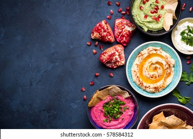 Colorful hummus bowls background. Different kinds of dips. Traditional hummus, herbs hummus, beetroot hummus, spread. Assorted meze and dips with crispy pita. Space for text. Meze and snacks concept