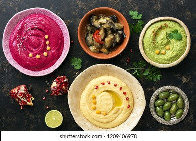 Colorful hummus in bowls on a dark rustic background, traditional hummus, hummus with basil, beet hummus. Top view, flat lay. Clean eating, dieting, vegetarian party food.