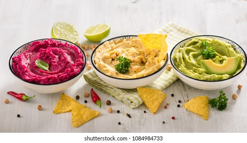 Colorful hummus, different dips, vegan snack, beetroot and avocado hummus, vegetarian eating