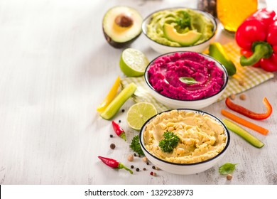 Colorful hummus, different dips, vegan snack, beetroot and avocado hummus, vegetarian eating
