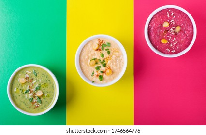 Colorful hummus in the white bowls against the geometric background. Classic, beetroot and spinach chickpea dips