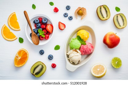 Colorful ice cream with mixed berry and various fruits raspberry ,blueberry ,strawberry ,orange ,kiwi ,apple,lemon and peppermint setup on white background . Summer and Sweet menu concept flat lay.