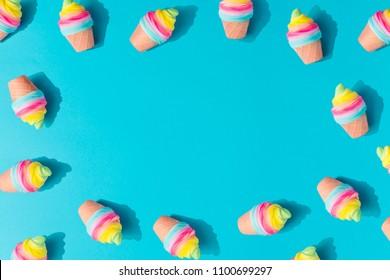 Colorful ice cream pattern on pastel blue background. Creative minimal summer flat lay.