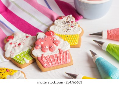 Colorful icing cookies in cupcake shape on white background and cornets with glaze for painting