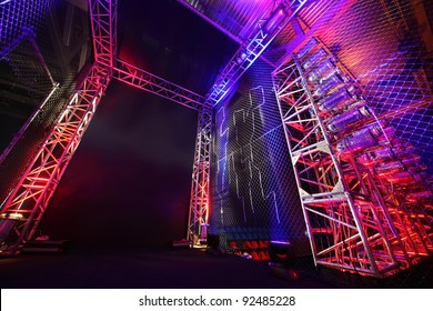 Colorful illuminated way with grid to boxing ring inside fight club; many lights