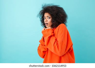 Colorful image closeup of scared woman in red shirt posing on camera and pressing arms to chest in fear isolated over blue background